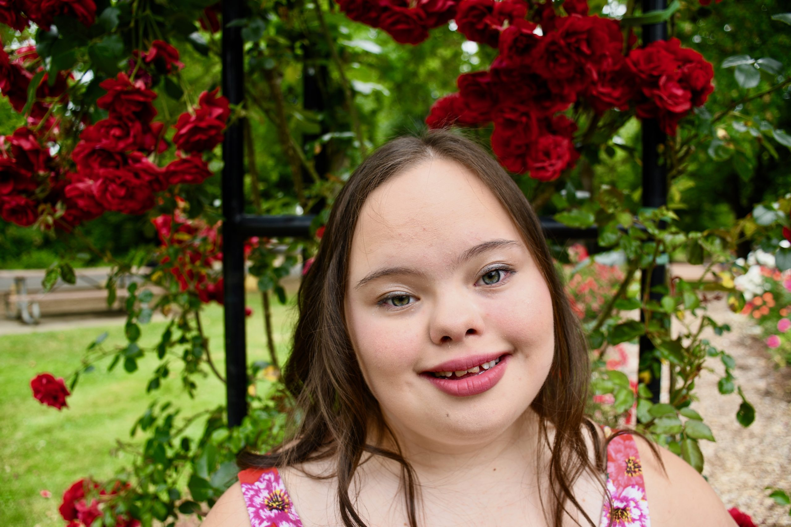 Photo of Laura Estreich, a young white girl with Downs syndrome. She has long brown hair and she is wearing a floral dress. Laura is smiling at the camera. She is standing in front of a red rose bush
