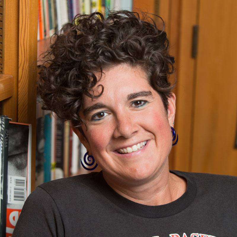 Photo of Allison Hobgood, a 40-something white woman with short, dark curly hair. She is wearing spiral earrings and a dark t-shirt. She is smiling at the camera. Behind her is a partially-visible bookcase with some books peaking out.