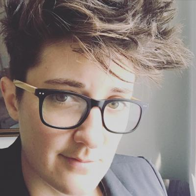 Close-up photo of Abby Mulcahy, a 30-something genderqueer person. Abby is wearing dark-framed glasses. Abby has short, dark wavy hair. Abby is wearing a dark blazer.