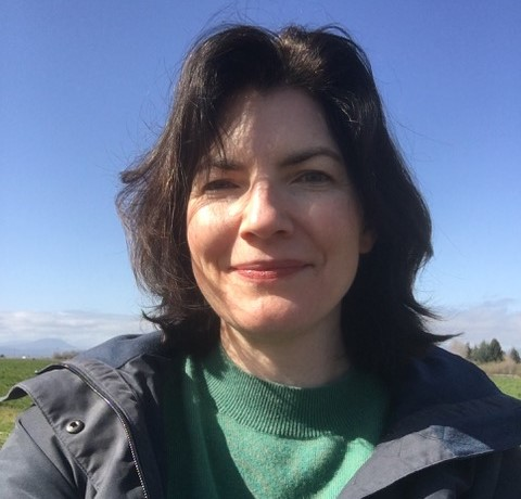 Selfie photo of Rebecca Olson, a white woman with shoulder-length dark brown hair. She is smiling at the camera. She is wearing a green sweater with a dark blue jacket.